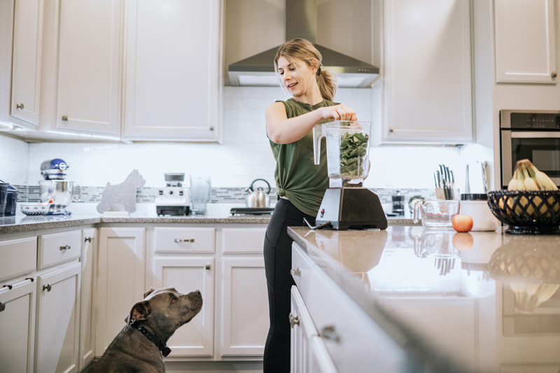 Woman Mixing Protein Smoothie with dog watching
